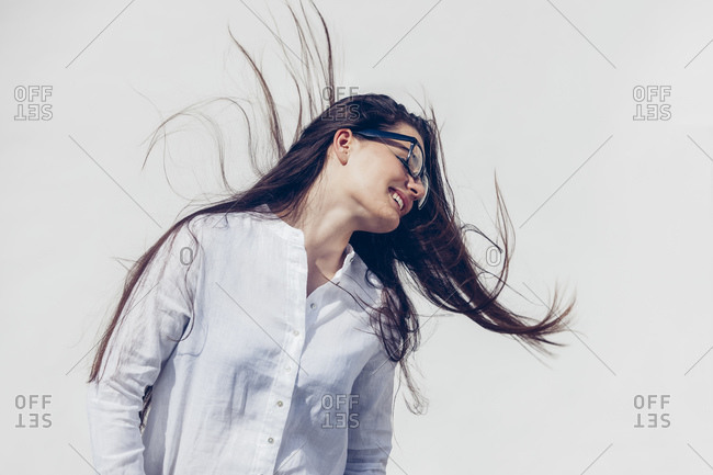Young woman with glasses wearing white blouse tossing her hair in front of white background