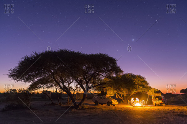 Campsite with campfire under starry sky, Central Kalahari Game Reserve, Kalahari, Botswana