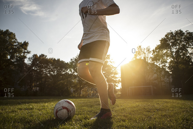 Teenager playing soccer on soccer pitch