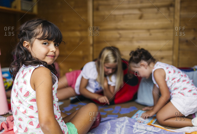 Little girls playing in a little wooden cottage