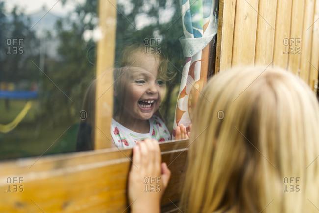 Little girls playing through a glass window