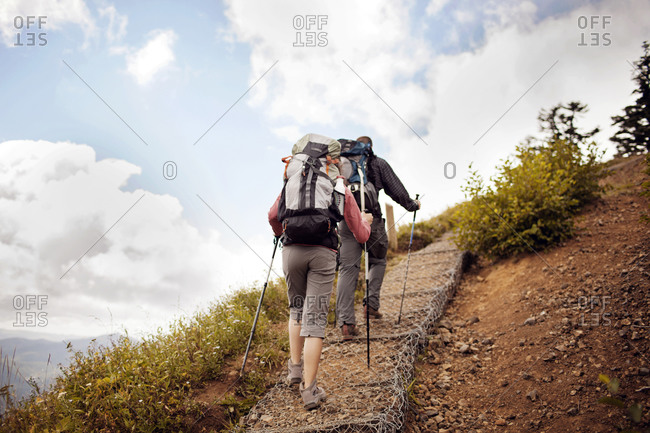 Couple hiking up a steep path in Oregon