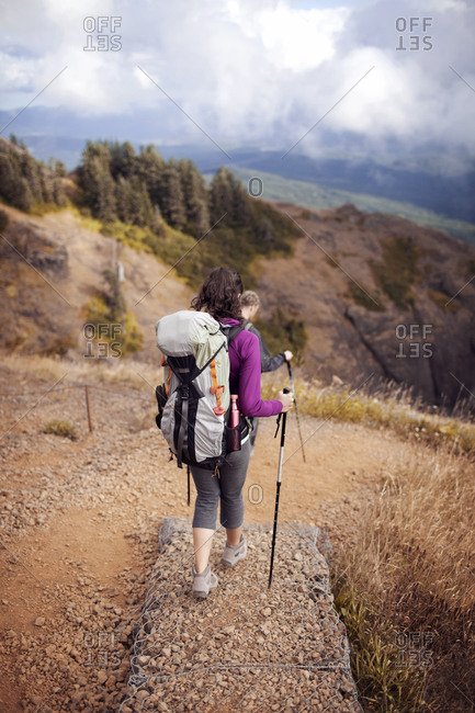 Couple hiking down a steep trail in Oregon