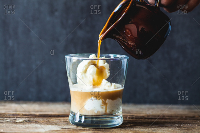 Vanilla ice cream being topped with hot espresso to make affogato dessert