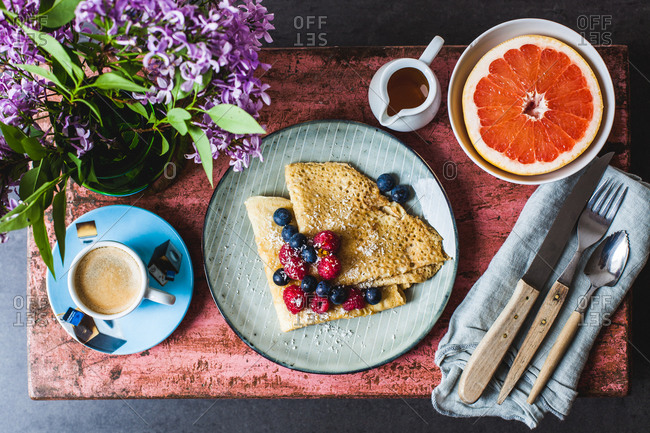 Overhead view of breakfast table setting of berry crepes, espresso and grapefruit
