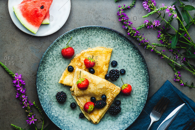 Plate of fresh berry crepes and watermelon