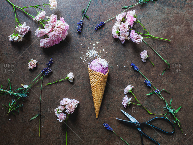 Berry ice cream cone on rustic stone surface surrounded by fresh cut flowers