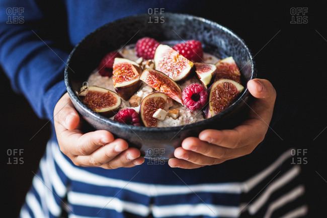 Child holding dish of oatmeal with fresh figs and berries