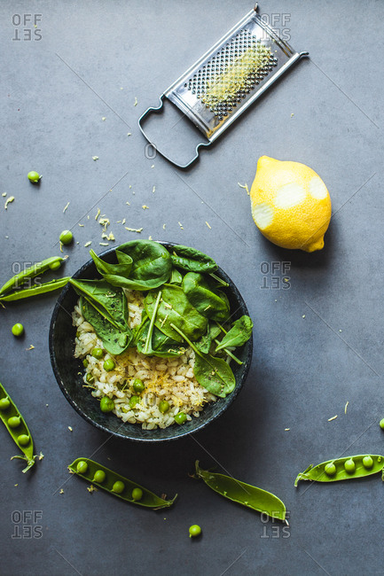 Pea and lemon risotto on stone surface with citrus rind grater