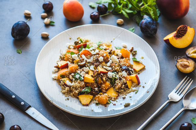 Quinoa, stone fruits and feta salad on stone countertop