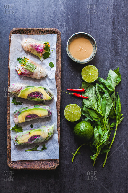 Tray of transparent vegetable Vietnamese summer rolls with peanut dipping sauce