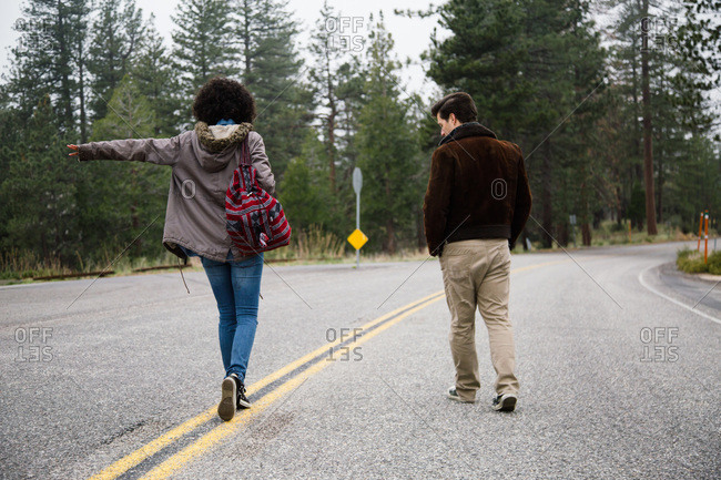 A couple walks down the middle of a street in a forest