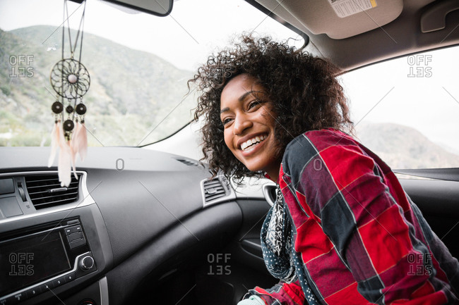A young woman smiles in the front seat of a car