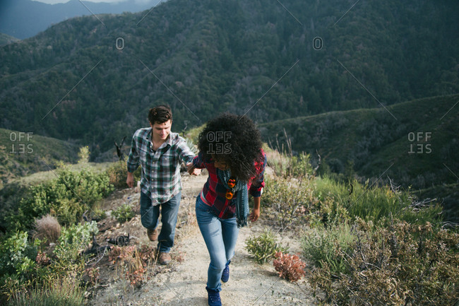 A couple hikes up a dusty trail on a mountain