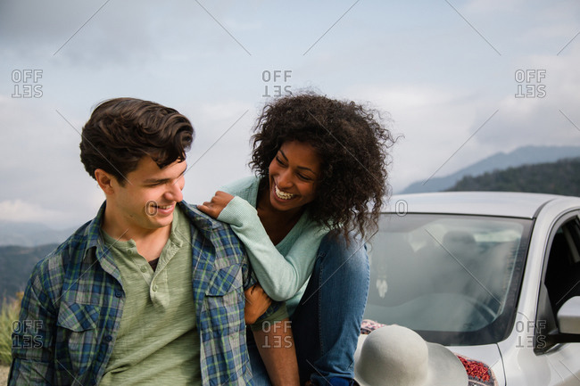 A couple sits on the hood of a car and smiles
