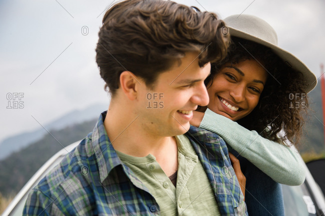 A young woman leans on her boyfriend and smiles