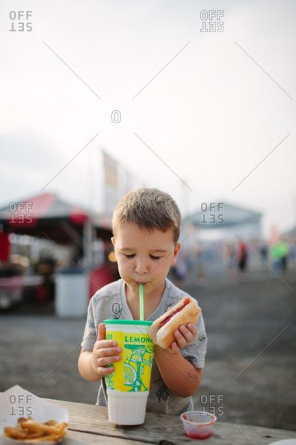 A boy eats a hot dog and drinks lemonade at a country fair