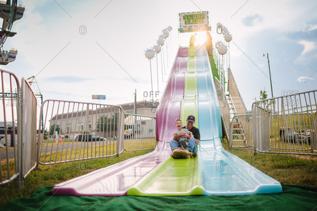 A father and son slide down a super slide at a country fair