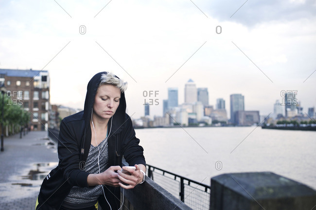 Woman with ear buds and a smartphone