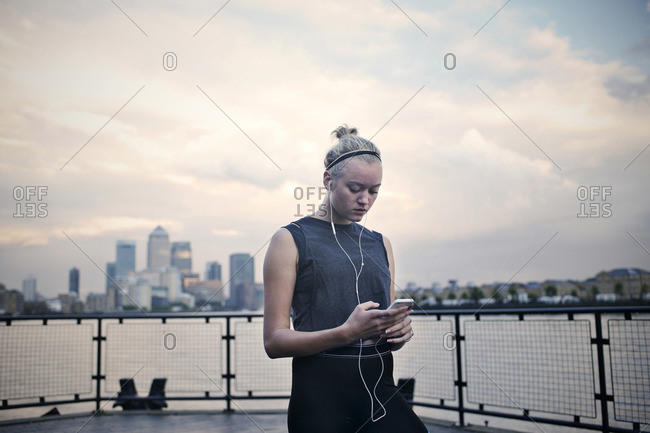 Young woman selects music before working out