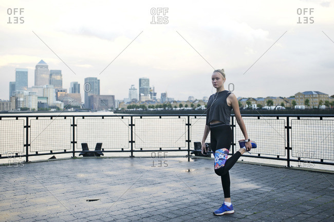 Young woman stretching at a waterfront