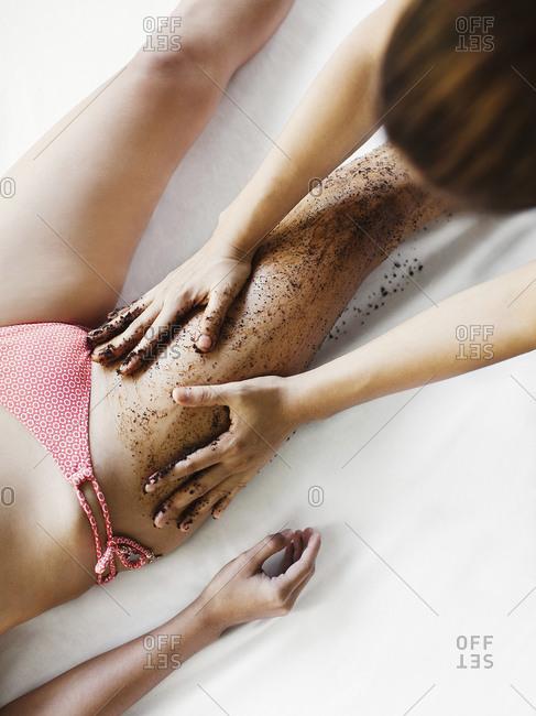 Spa technician applying coffee bean scrub to skin on woman's legs