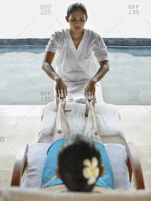 Woman receiving Thai reflexology treatment outside by pool