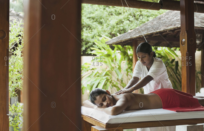 Woman receiving a deep tissue massage at an outdoor spa