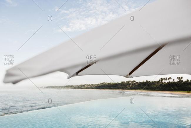 Beach umbrella and oceanfront infinity pool at resort in Sri Lanka