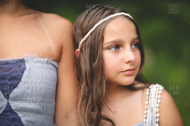 A girl in a headband leans against her mother