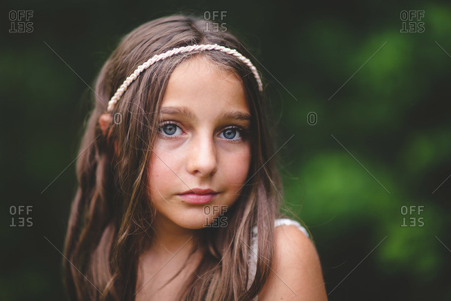 A girl in a white headband stands outside