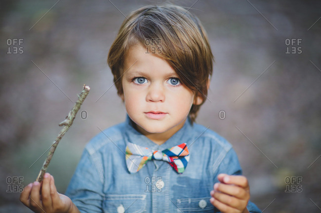 A boy in a bowtie holds a stick