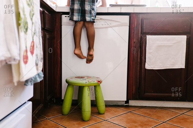 Boy using stool to climb on kitchen counter