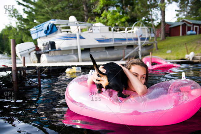 Puppy jumping on floatie with girl