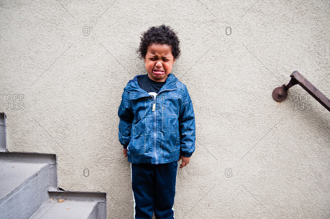 Child crying on steps by wall