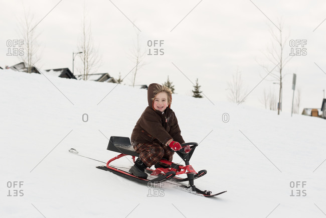 Boy smiling sledding with steerable sled