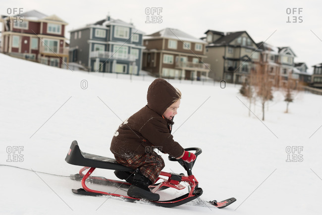 Boy laughing sledding with steerable sled