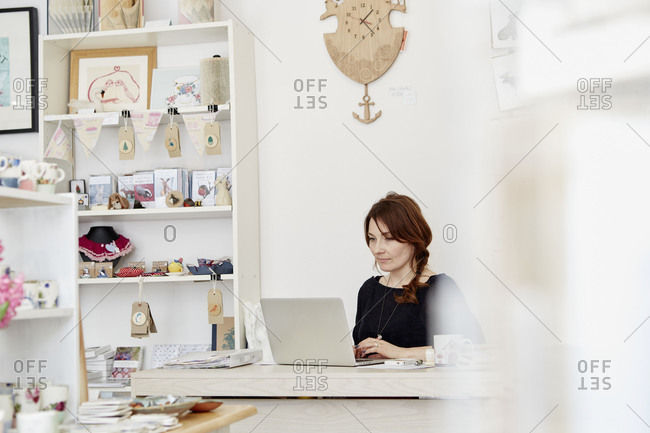 A woman in a small gift shop managing her business on a laptop