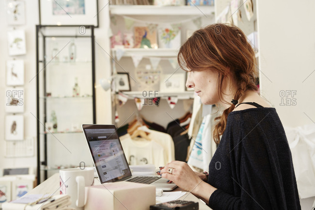 A woman in a small crafts shop working on a laptop