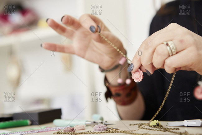 A woman seated at a workbench putting a small floral pendant on a gold chain