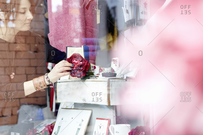 A woman rearranging the window display of a craft store
