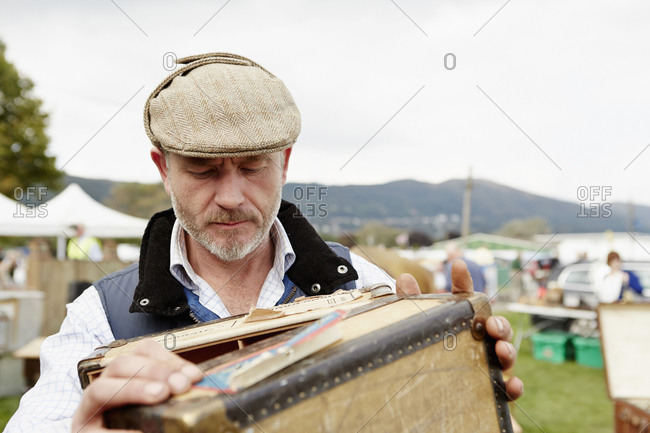 Man wearing a flat cap looking at a vintage suitcase at a flea market