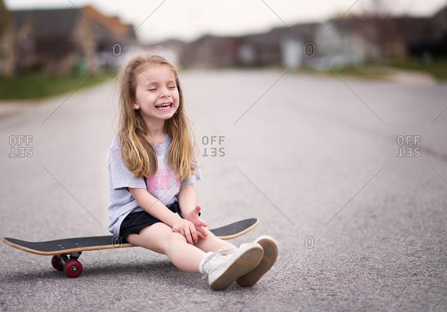 Smiling girl sitting on skateboard in middle of street