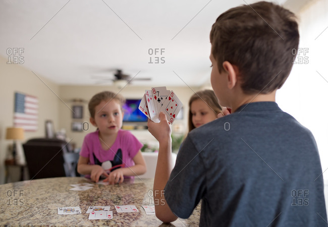 Three kids indoors playing card game