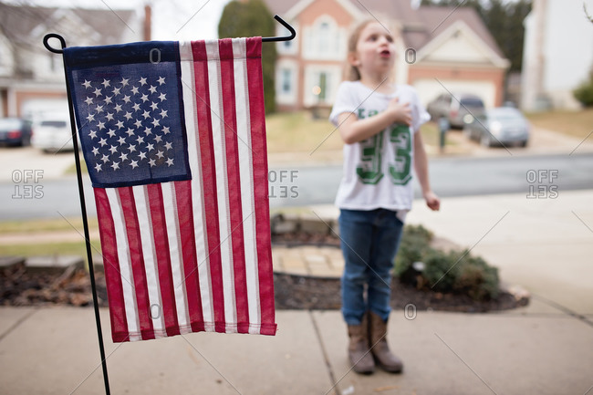 Patriotic girl on sidewalk by American flag