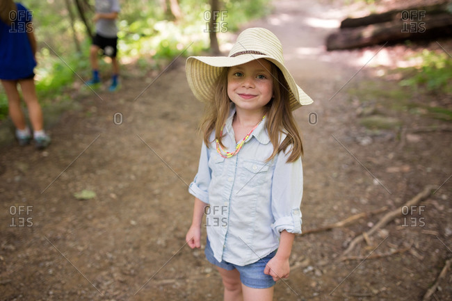Girl with a straw hat on forest trail