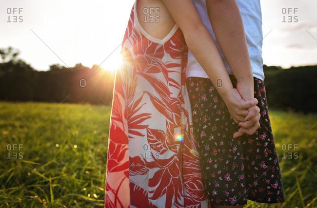 Two girls back to back in sunlit field
