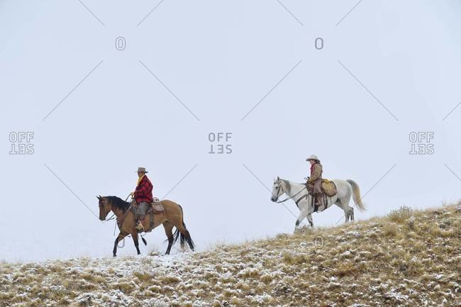Cowboy with young cowboy riding along horizon with snow, Rocky Mountains, Wyoming, USA