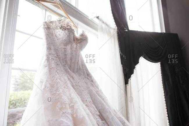 Wedding dress hanging by window