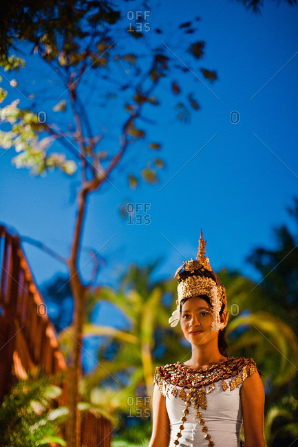 Siem Reap, Cambodia - February 24, 2009: A young Cambodian Apsara dancer walks on garden path at dusk at La Residence d'Angkor, Siem Reap, Cambodia